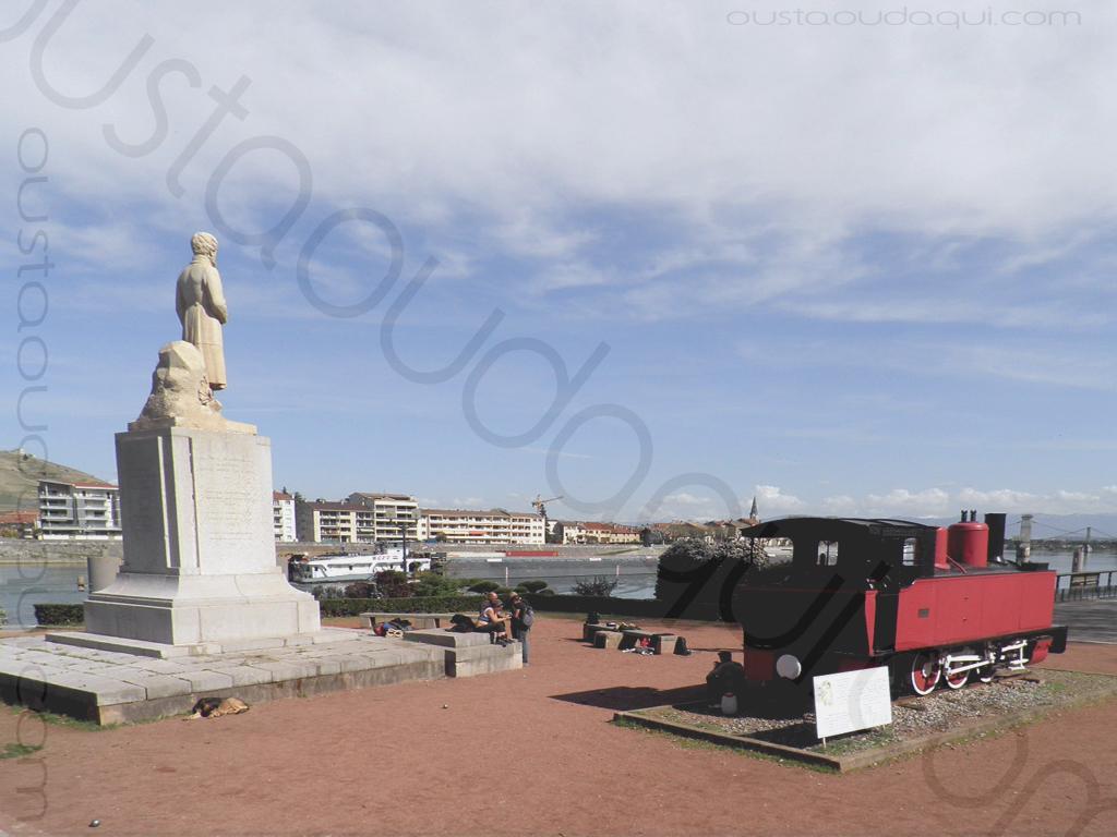photographie prise le long de l' EuroVelo 17:  la locomotive à vapeur Pinguely 103 et la statue de Marc Seguin à Tournon en Ardèche